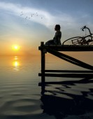 Fotografie Silhouette of peaceful person sitting on pier at sunset