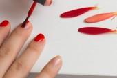Aplikace Červený lak na nehty na ruce s červených okvětních lístků květin