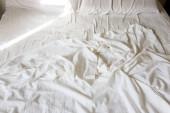 zmačkaný bílý prostěradlo v posteli