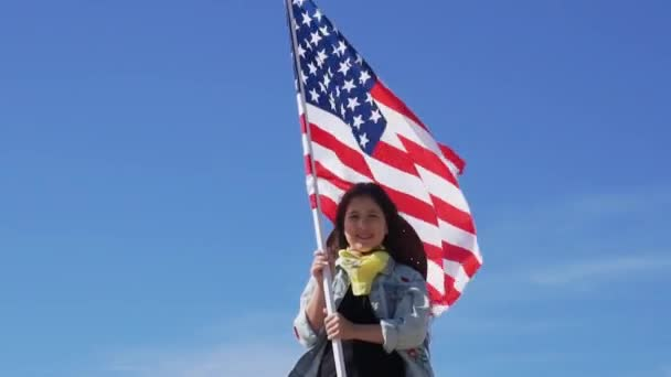 Independence Day. Patriotic holiday. Beautiful happy girl with black long hair with American flag on a bright sunny day. USA celebrate 4th of July.