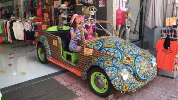 Mexiko, cancun - am 29. Dezember sitzt ein schönes Mädchen mit rosa Hut in einem Auto mit einem Skelett und lächelt. Feiertag ist der Tag der Toten. Reisekonzept.