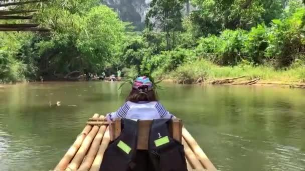 Egy csoport a turisták lebeg a folyón. Lány 9 éves vitorlázás egy tutajon egy folyón Ázsiában. Utazási koncepció.