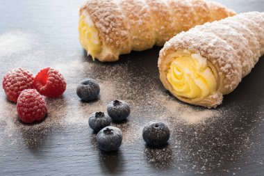 Cream filled horn pastries with berries and powdered sugar