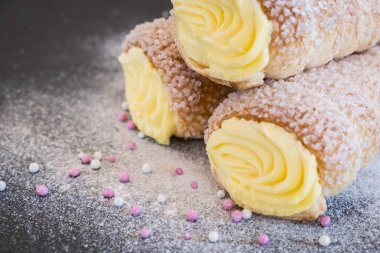 Puff pastry horns filled with vanilla cream, powdered sugar and topping