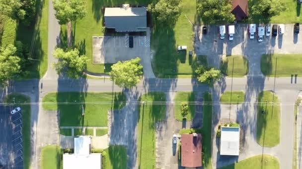Letecký pohled na typickou americkou předměstskou oblast zobrazující směsici obytných, komerčních a přírodních prostorů spojených ulicemi a venkovskými silničními cestami s pruhy prostorů pro parkoviště, trávníky, stromy, keře a další plantáže.