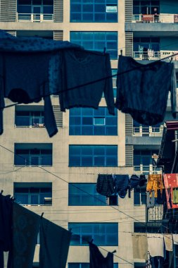 Laundry is hanging on the clothesline. Ropes are pulled between houses in the city. The clothes are air dried. Sunny. Day. Georgia.