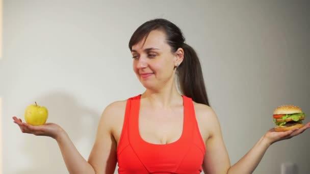 Sportliche Frau wählt zwischen Apfel und Sandwich