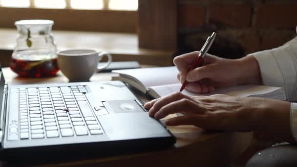 Woman Taking Notes in a Notebook and Using Laptop