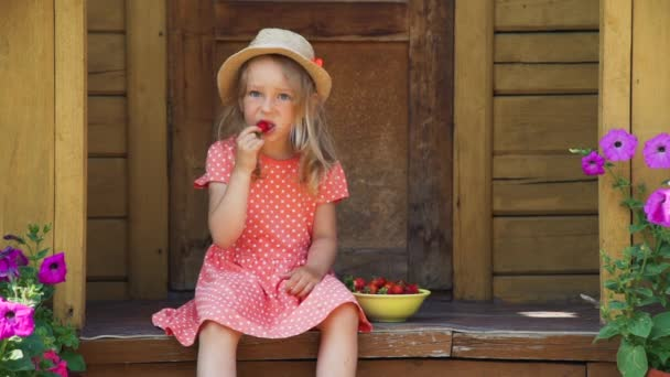 Little Girl in Straw Hat Eating Fresh Strawberry