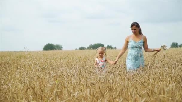 Malá holčička s mámou procházející pšenicí pole