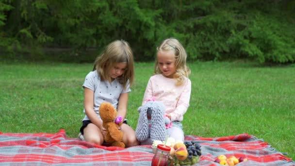 Malé holčičky hrají s hračkama v parku