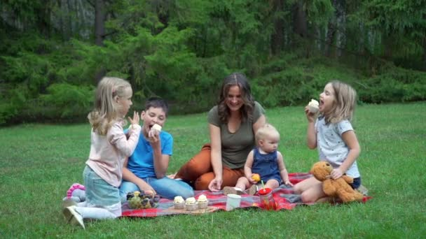 Woman and Children Tasting Cupcakes Outdoors