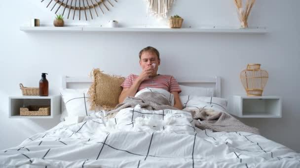 Nemocný muž leží v posteli s vysokou horečkou a chřipkou