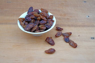Plateful of Organic Raisins and Spilled Raisins on Wooden Background