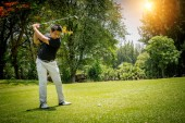 Rozmazaný golfista hraje golf na večerním golfovém hřišti, na slunci s