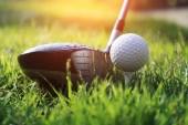 Golfová koule a golfový klub na krásném golfovém hřišti při západu slunce