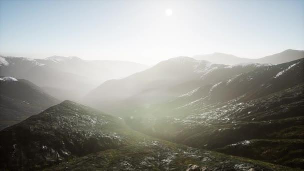 hory v mlze při západu slunce