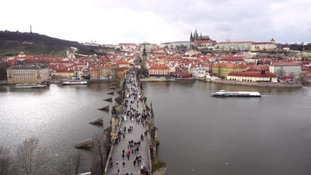 Karlův most s lidmi na něm shora s lodí