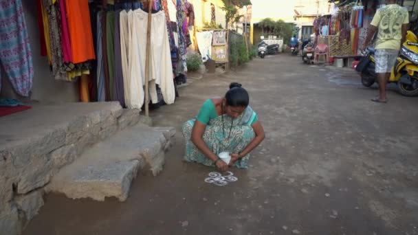 A woman draws a prayer drawing on the ground.