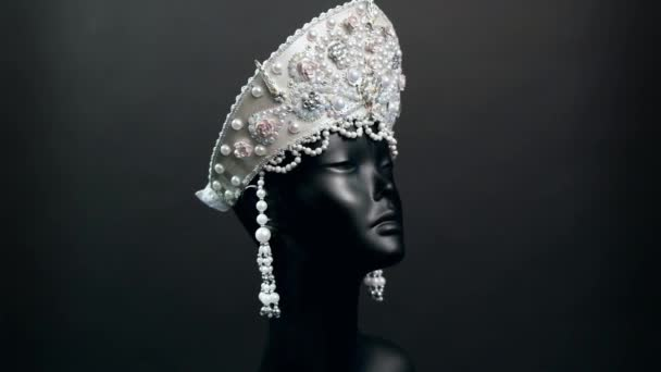 Head of mannequin in creative white kokoshnick with jewels and pearls, black studio background