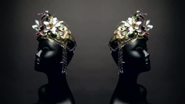 Black head of mannequin in creative metal crown decorated with flowers on dark studio background
