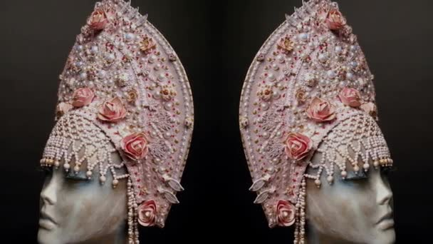 Head of mannequin in creative pink kokoshnick with roses and pearls, dark background