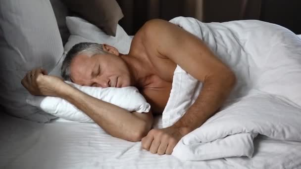 A man sleeps sweetly in bed in sunny morning.