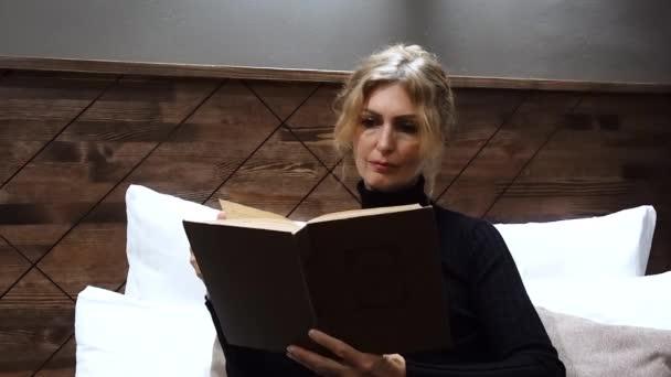 Krásná žena, která čte knihu a usmívá se v posteli.