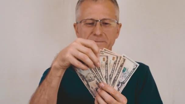Starší muž ukazuje své příjmy v dolarech a je šťastný.