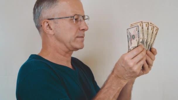 Starší muž s brýlemi spočítá dolary a pak na ně ukazuje.