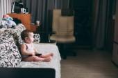 egy kislány, egy távoli-a kanapén tévénézés a saját