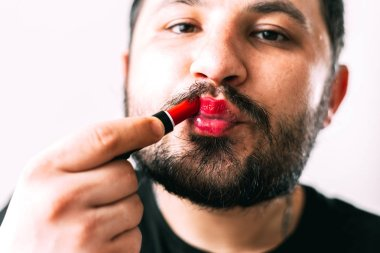 a man paints his lips with lipstick