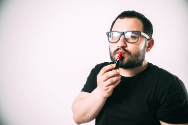 a man in glasses with a beard paints his lips with red lipstick