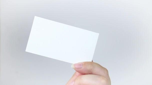 Fehér névjegykártya lap szürke alapon. Egy kéz tart egy névjegykártyát és eltűnik. Üzleti koncepció. Videóklip hd
