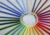 Pencils circle which lies on a wooden background
