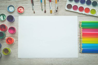 Tools for drawing, stationery, artist's workplace. Paint and pencils and blank paper on wooden table, top view, flat lay, copy space. school drawing supplies