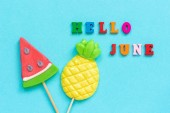 Hello June colorful text, pineapple and watermelon lollipops on stick on blue paper background. Concept vacation or holidays Creative Top view Template Greeting card, postcard