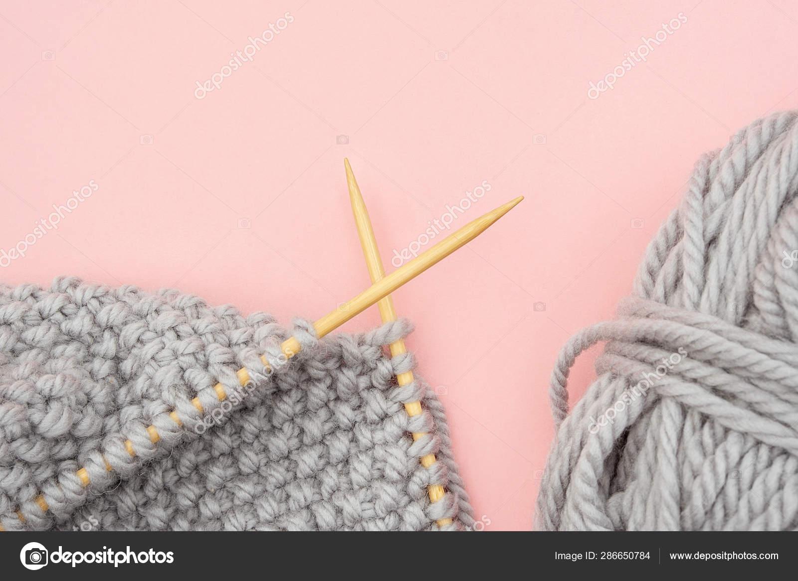38fd1a84e8d2 Pieza de tejido de punto gris sobre agujas de madera de bambú con ...