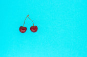 two ripe red cherries on blue background, copy space