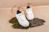 Ethisch-vegane Schuhe. Ein Paar weiße Turnschuhe mit trockenen Blumen auf Baumrinde und Moos, Hintergrund neutrales beiges Bastelpapier.