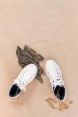 Ethisch vegetarisches Schuhkonzept. Ein Paar weiße Turnschuhe mit trockenen Blumen auf Baumrinde und Moos, Hintergrund neutrales beiges Bastelpapier.