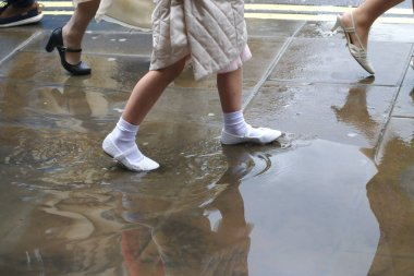 A well-dressed girl in white shoes goes from school through the puddle after heavy rain