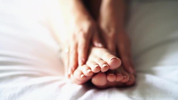 eine Frau massiert seinen müden, schmerzenden Fuß.