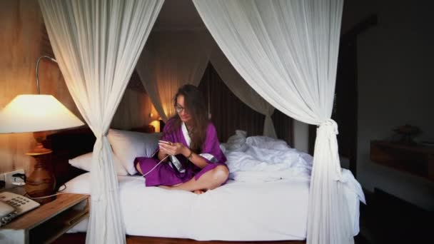 Beautiful woman using phone in bed managing smart connected home with mobile app