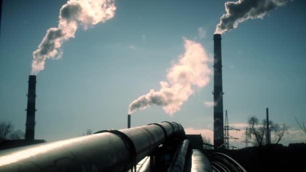 Heizungsnetzrohre und Rauch steigen aus dem großen Schornstein am blauen Himmel auf. Statischer Schuss