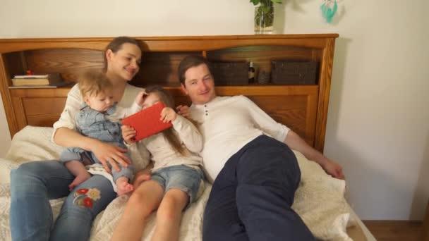 Rodiče s dětmi se v posteli baví. Ruční snímek