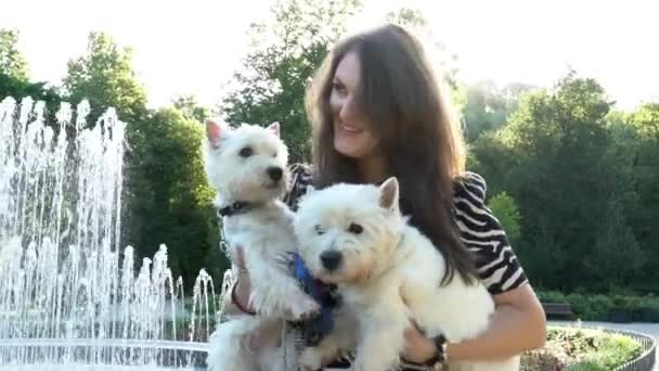 fröhliche Frau mit Hunden in der Hand in der Nähe des Brunnens im Park. Handschuss