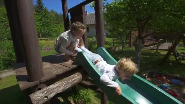 Hyperactive children slide down on playground. Kid play and laugh. Handheld