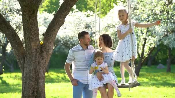 Mosolygó szülők és lányaik lányok swing virágzó almafa kert