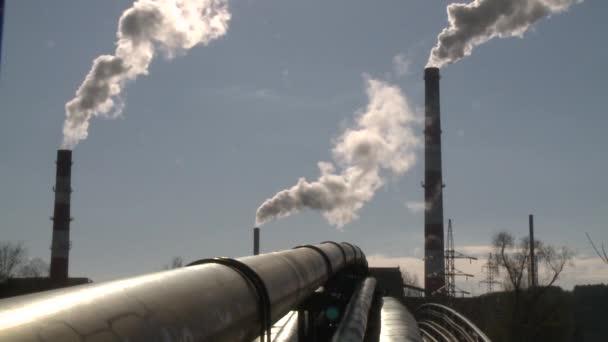 Heizungsrohre und Rauch steigen aus einem großen Schornstein am blauen Himmel auf. Statischer Schuss
